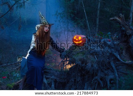 Beautiful witch with a pumpkin in the magic forest - stock photo