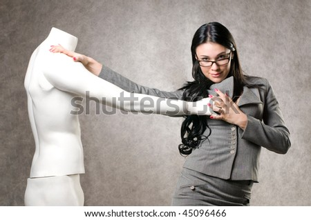 Beautiful woman and a male mannequin in studio - stock photo