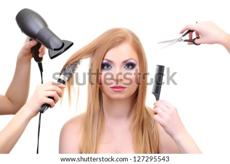 Beautiful woman and hands with brushes, scissors and hairdryer isolated on white - stock photo