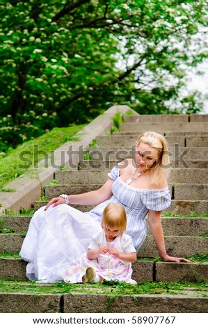beautiful woman and her adorable baby daughter sit on a stone steps - stock photo