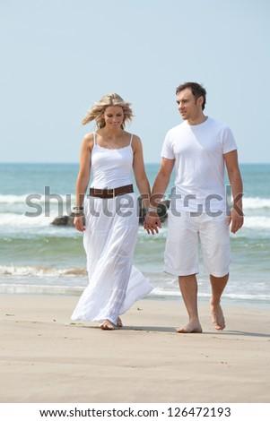 Beautiful woman and man walking on beach - stock photo