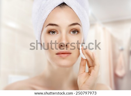 beautiful woman applying cosmetic cream - stock photo