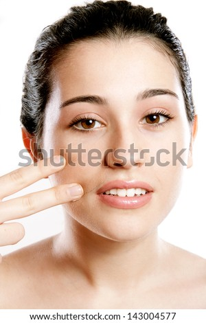 Beautiful woman applying foundation on face with fingers as war painting - stock photo