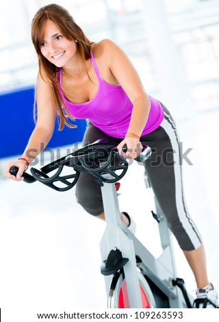Beautiful woman at the gym on bike - stock photo