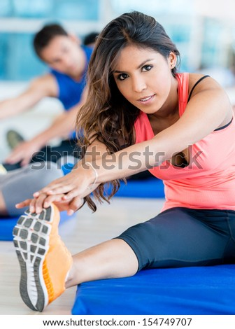 Beautiful woman at the gym stretching her leg  - stock photo