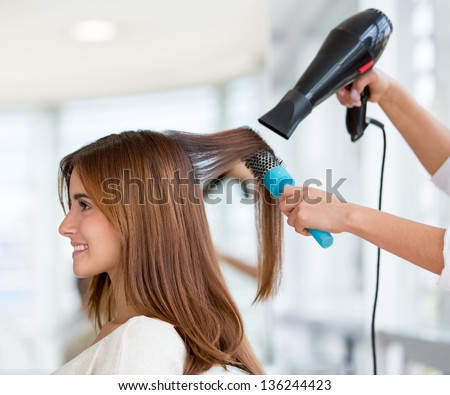 Beautiful woman at the hairdresser blow drying her hair - stock photo