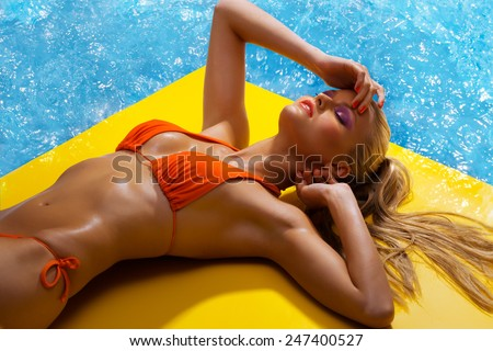Beautiful woman at the swimming pool. - stock photo