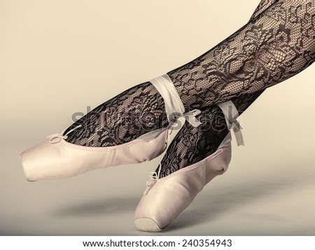 beautiful woman ballet dancer, part of body legs in shoes and black lace tights studio shot on gray background - stock photo