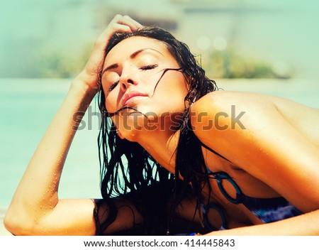 Beautiful woman beside swimming pool basking in the summer sun - stock photo