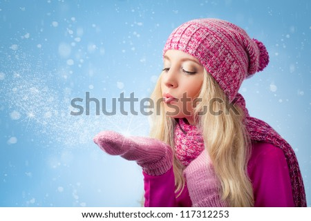 beautiful woman blowing to snowflakes over blue background - stock photo