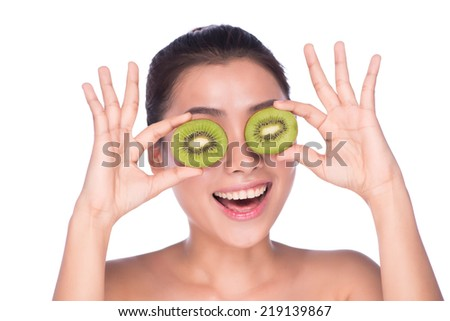 Beautiful woman cares for the skin face. Kiwi. Healthy fruit funny woman holding kiwi fruit for her eyes - posing at studio isolated on white - stock photo