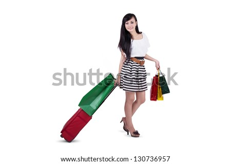 Beautiful woman carry bags and luggage isolated on white - stock photo
