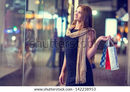 Beautiful woman carrying many shopping bags on a city street - stock photo