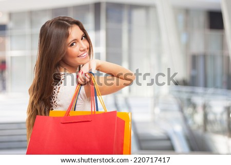Beautiful woman carrying shopping bags - stock photo