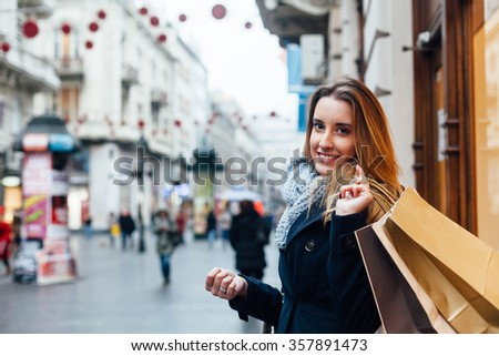 Beautiful woman carrying shopping bags on a city street - stock photo