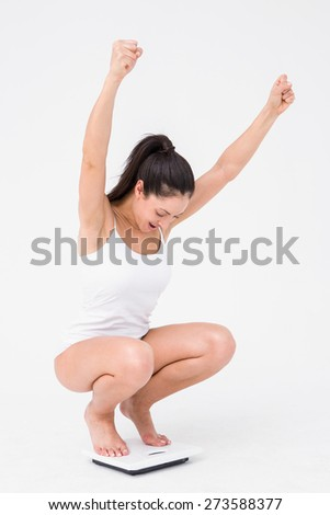 Beautiful woman cheering on weighing scales on white background - stock photo