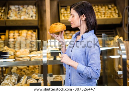 Beautiful woman choosing her bread in supermarket - stock photo