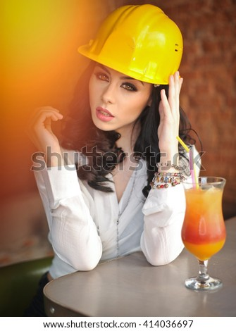 Beautiful woman civil engineer with yellow helmet taking a break in front of orange juice. Young female architect with white shirt drinking a juice in restaurant. Young female construction specialist - stock photo