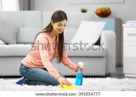 Beautiful woman cleaning carpet with sponge and spray - stock photo