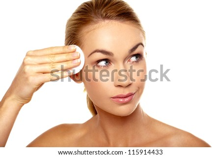 Beautiful woman cleansing her temple using lotion on a cotton pad in a personal hygiene and skincare concept - stock photo