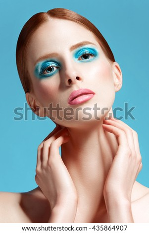 Beautiful woman close up, high-quality beauty on blue background - stock photo