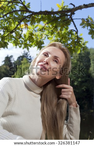 beautiful woman combs long hair in the summer day on the river bank - stock photo