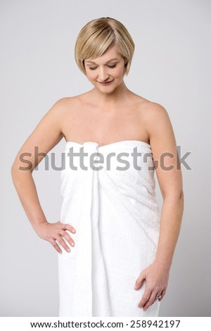 Beautiful woman covering herself with towel - stock photo