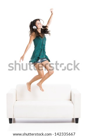 Beautiful woman dancing and jumping  over the sofa, isolated in white - stock photo