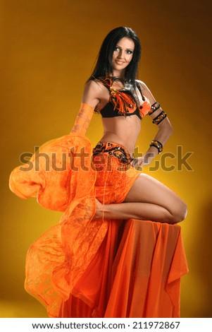 beautiful woman dancing in colorful Arabic dance costume.girl in an orange dress. beautiful brunette. long hair - stock photo