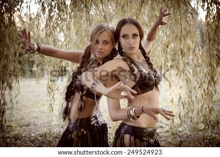 Beautiful woman dancing tribal near the large willow tree - stock photo