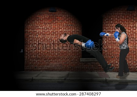 Beautiful woman delivering a knockout punch to a man - stock photo