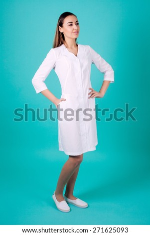 Beautiful woman doctor holding on turquoise background - stock photo