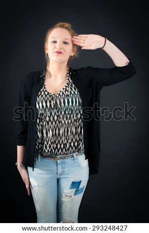 Beautiful woman doing different expressions in different sets of clothes: at attention - stock photo