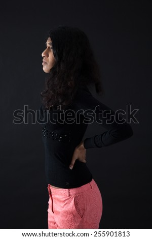 Beautiful woman doing different expressions in different sets of clothes: backache - stock photo