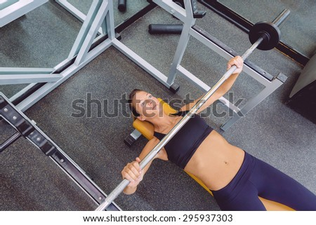Beautiful woman doing exercises with barbell on a bench press training in a fitness center - stock photo