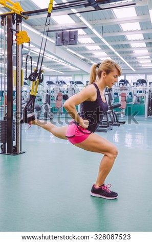 Beautiful woman doing hard suspension training with fitness straps in a fitness center. Healthy and sporty lifestyle concept. - stock photo