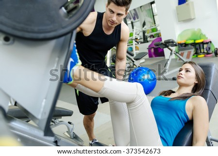 Beautiful woman doing leg exercises in gym with the help of personal trainer - stock photo