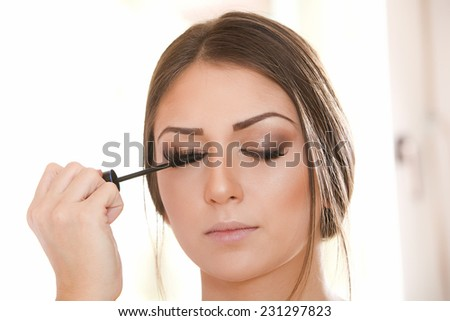 Beautiful woman doing make-up with eyeliner on eye - stock photo