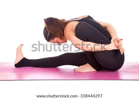 Beautiful woman doing Marichyasana pose on yoga class. Studio shot. - stock photo