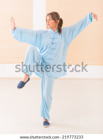 Beautiful woman doing qi gong tai chi exercise wearing professinal, oryginal chinese clothes at gym - stock photo