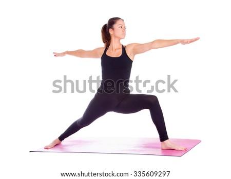 Beautiful woman doing Virabhadrasana 2 pose on yoga class, Studio shot. - stock photo