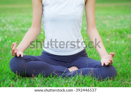 Beautiful woman doing yoga exercise in the park - stock photo