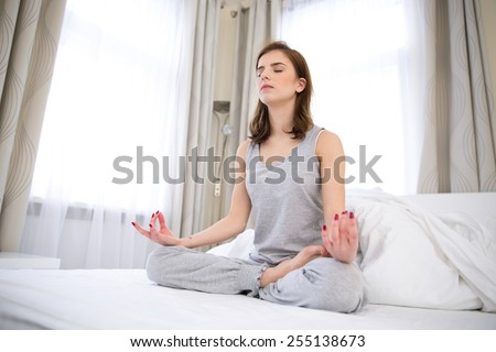Beautiful woman doing yoga exercises on the bed at home - stock photo