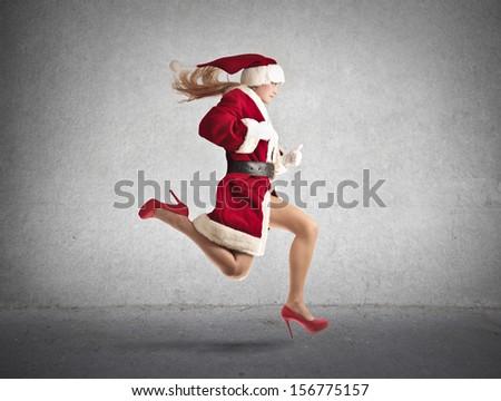 beautiful woman dressed as Santa runs fast - stock photo