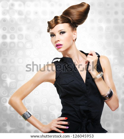 Beautiful woman dressed in black dress posing at studio - stock photo