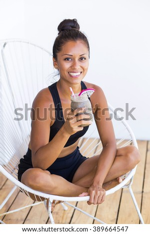 Beautiful woman drinking a smoothie sitting in a terrace - stock photo