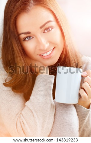 Beautiful woman drinking coffee at home - stock photo