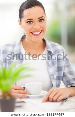 beautiful woman drinking coffee at home while calculating her financial - stock photo