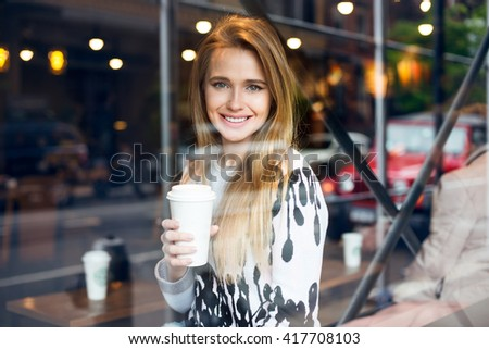 Beautiful woman drinking coffee at the cafe and looking at the camera thought the window - stock photo