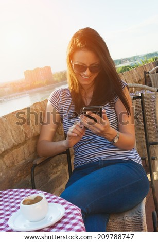 Beautiful woman drinking coffee in a cafe, using smartphone - stock photo